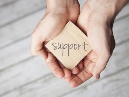"""Handen met bordje waar """"support"""" op staat"""
